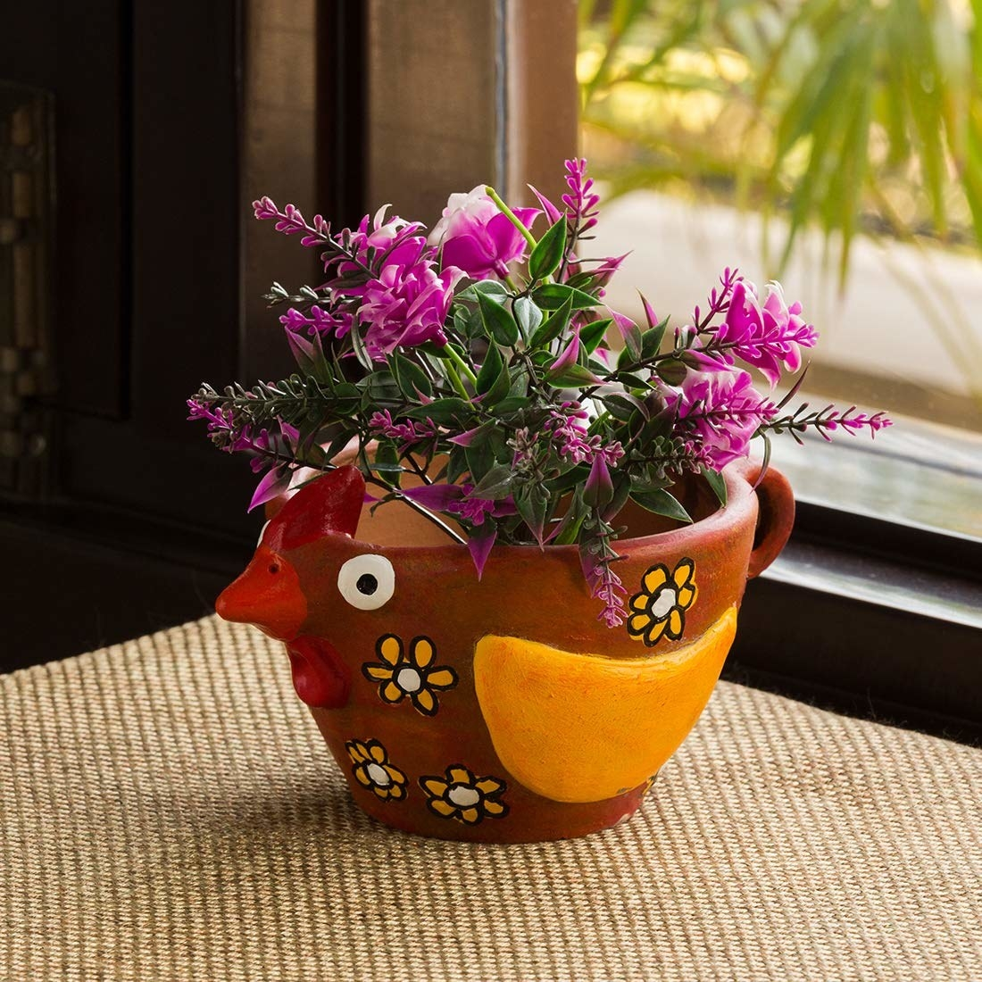 The terracotta planter painted to look like a bird with a red beak, yellow wings and whimsical flower all over it.