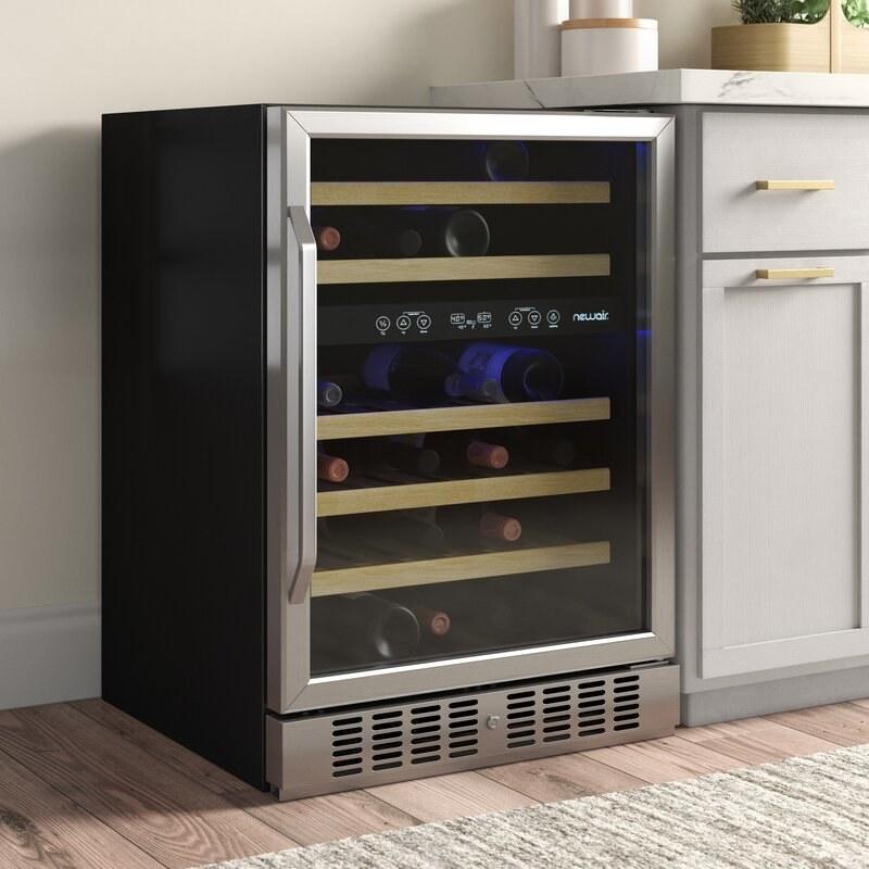 The fridge holding various bottles of wine