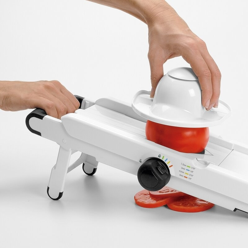 someone using the mandoline slicer with a tomato