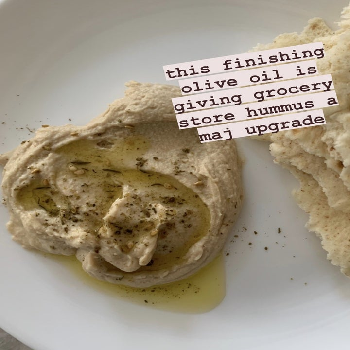 """A photo of hummus with olive oil drizzled on top and text """"this finishing olive oil is giving grocery sture hummus a maj upgrade"""""""