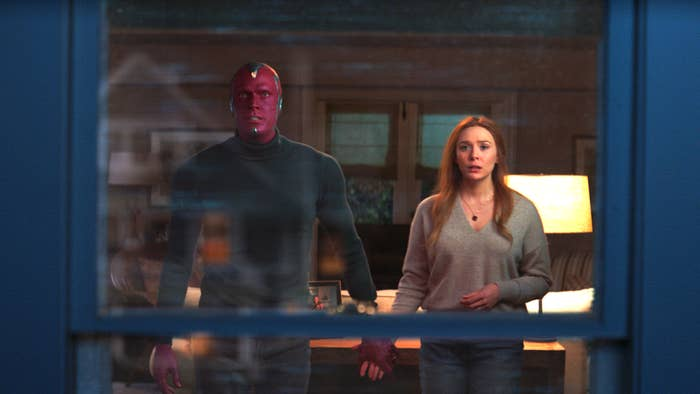 Vision and Wanda hold hands while looking out the window at something