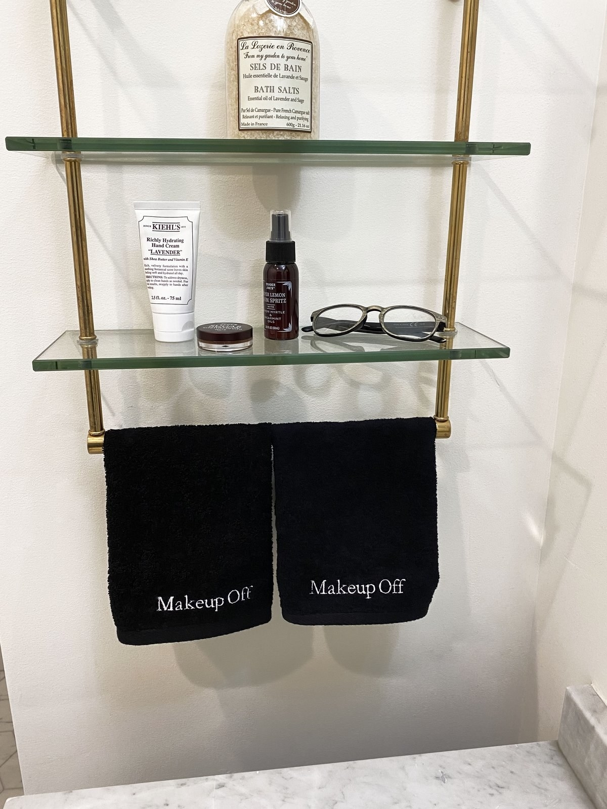 two of the black makeup towels hanging in a bathroom