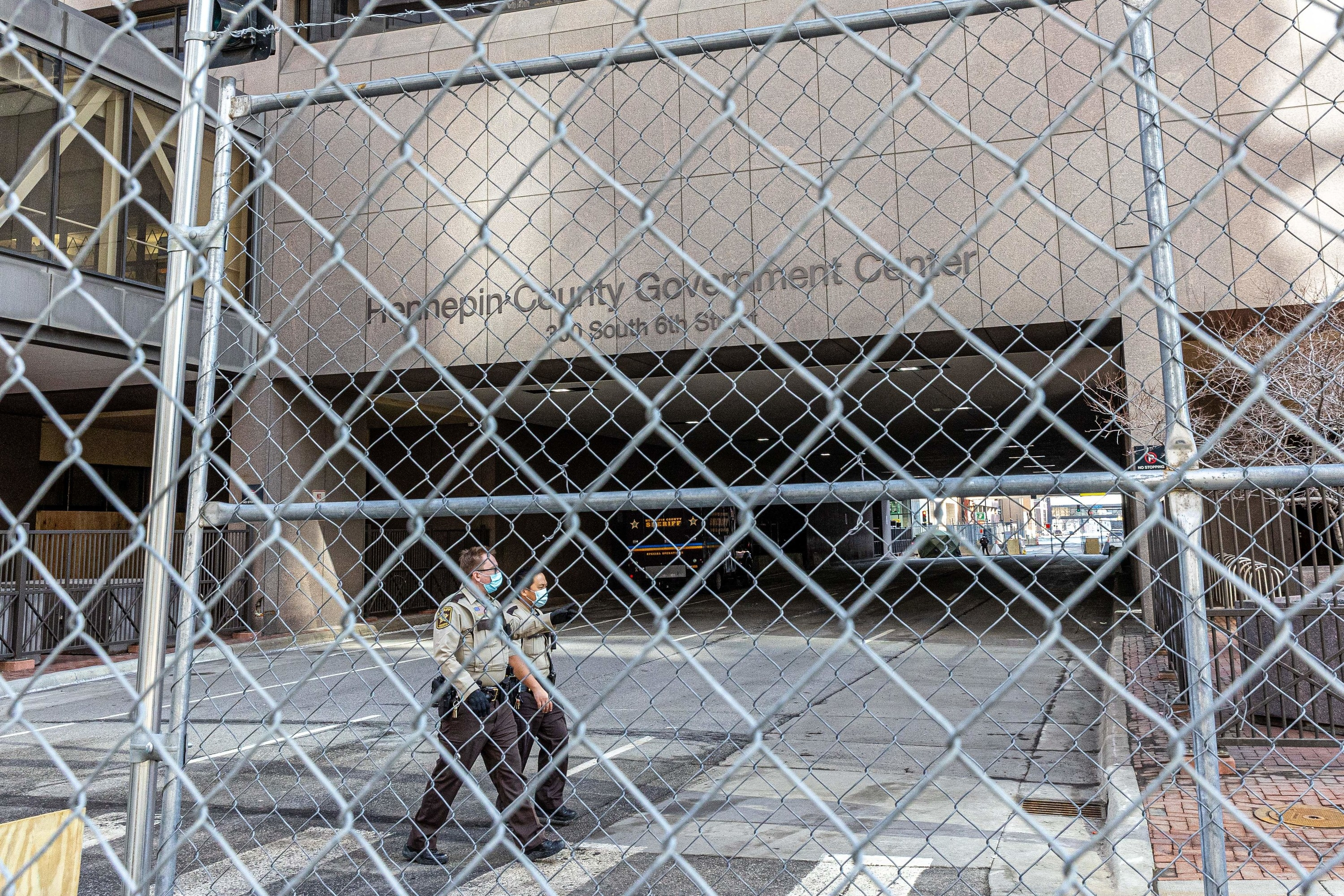 Masked police officers walk between fencing and the Hennepin County Government Center
