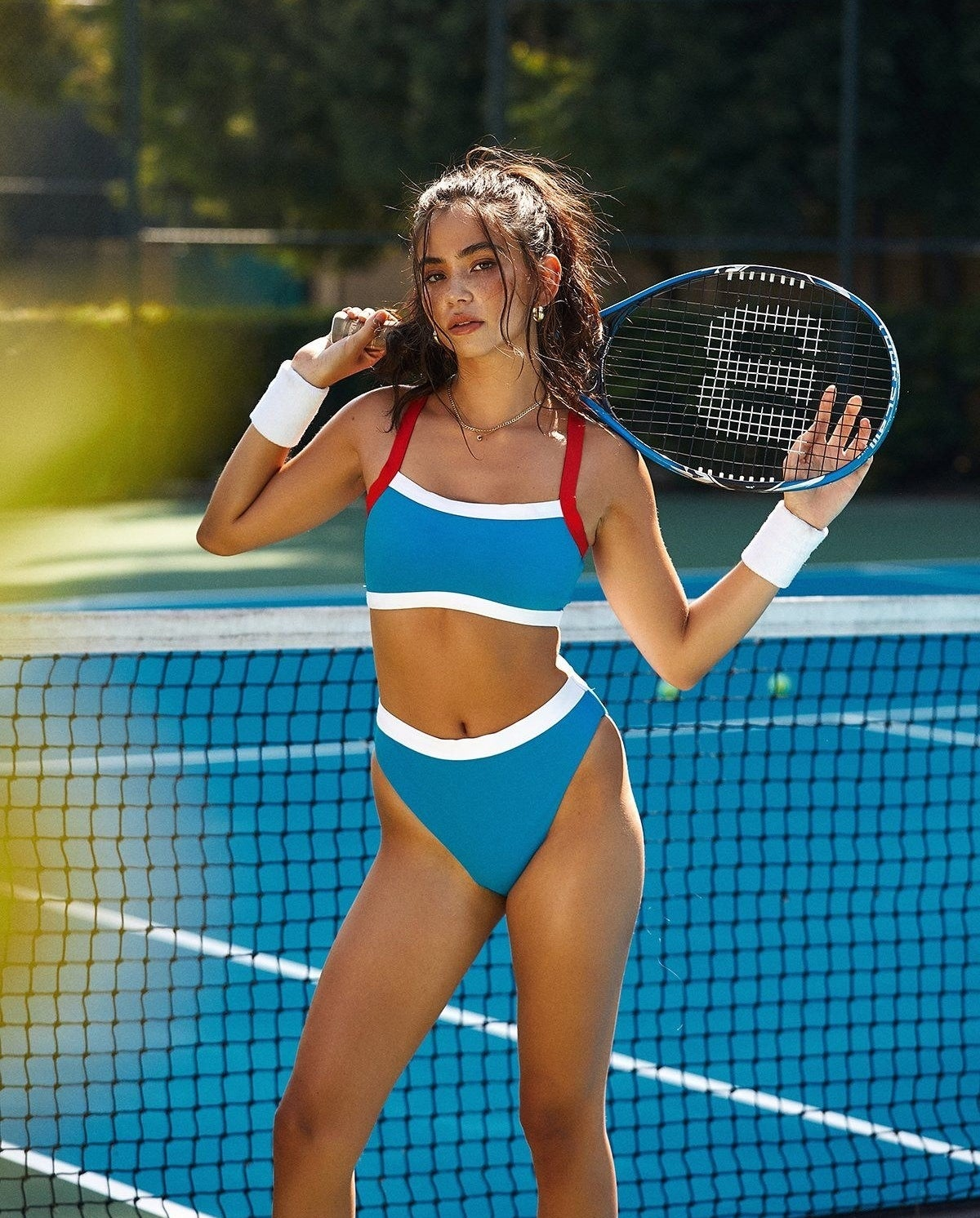 model wearing sporty swimsuit on a tennis court