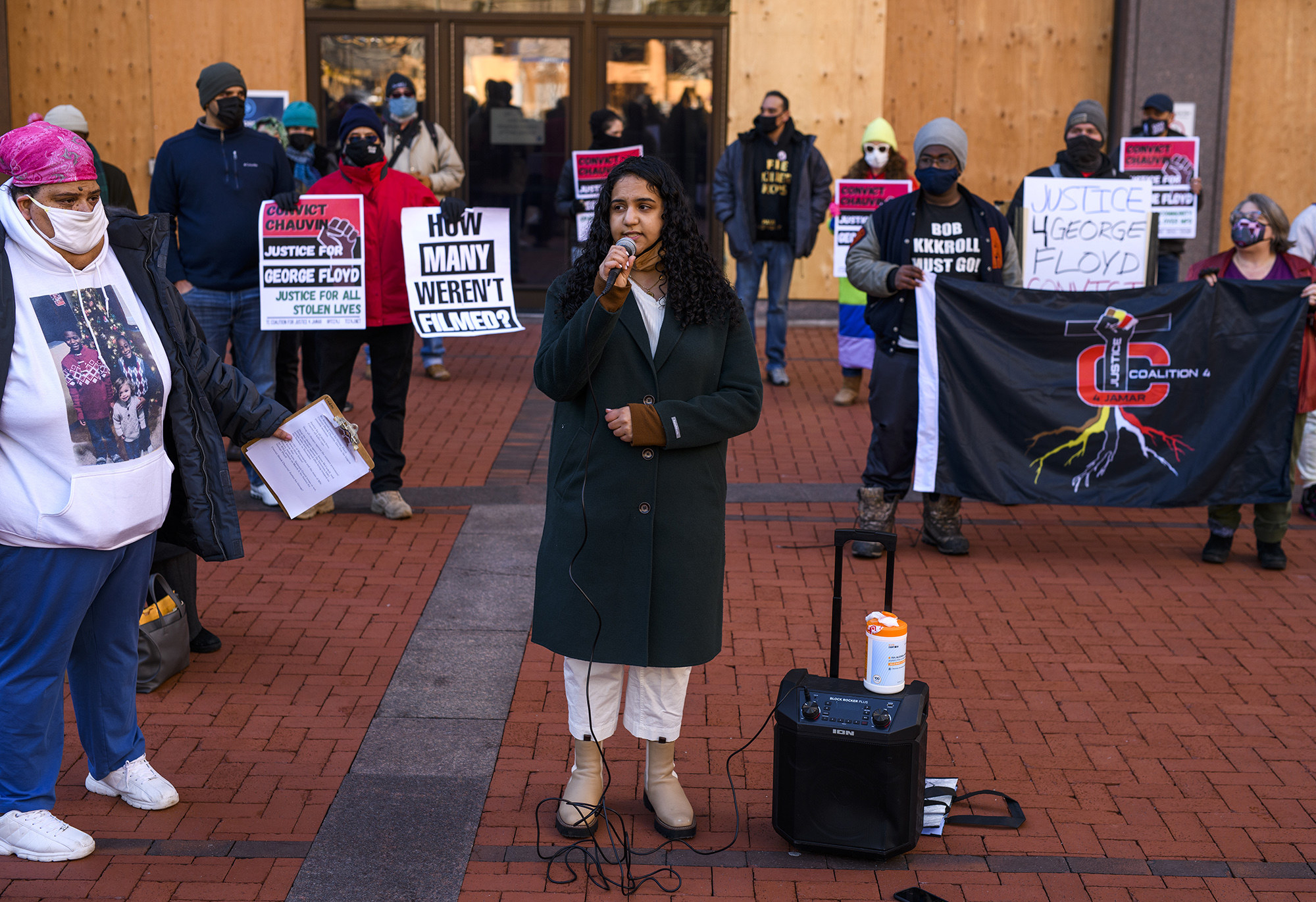 A person speaks into a microphone among a crowd of demonstrators at the government center