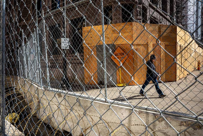 A person walks between the city hall building and a metal fence