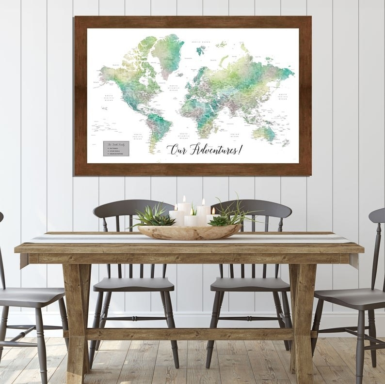 """framed world map above a kitchen table with the title """"Our Adventures!"""""""