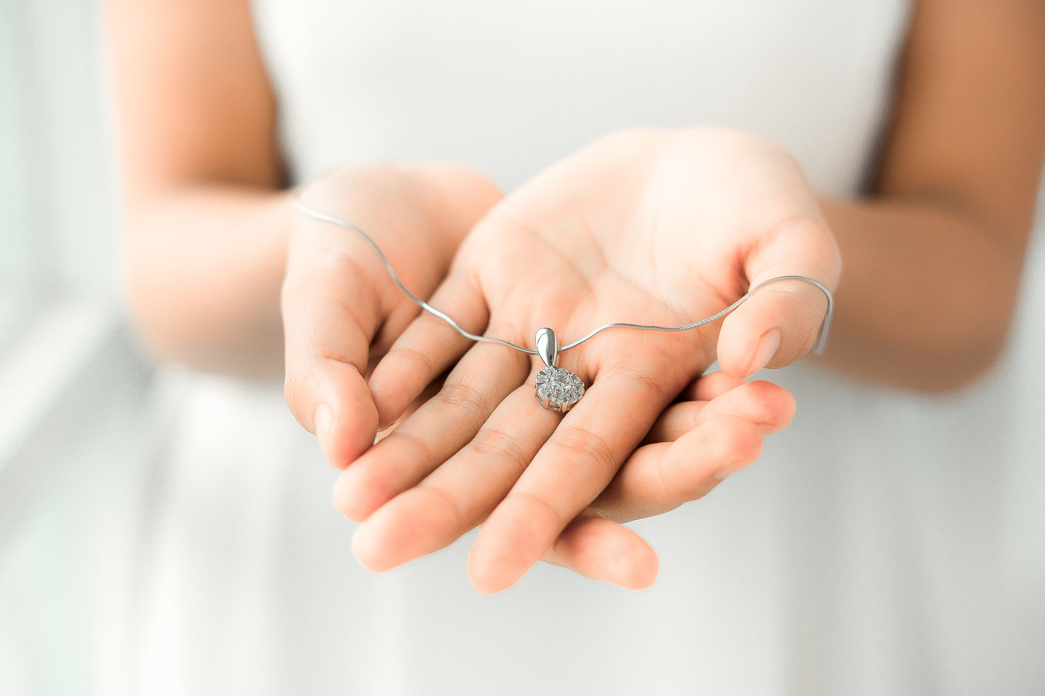 Person holding a necklace