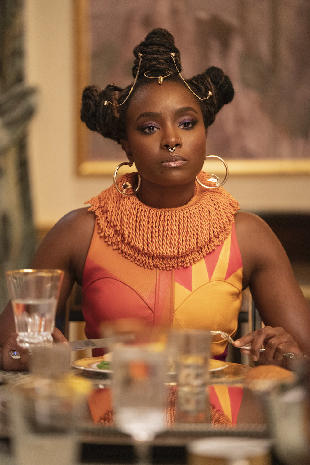 KiKi Layne sits at a dining table in COMING 2 AMERICA