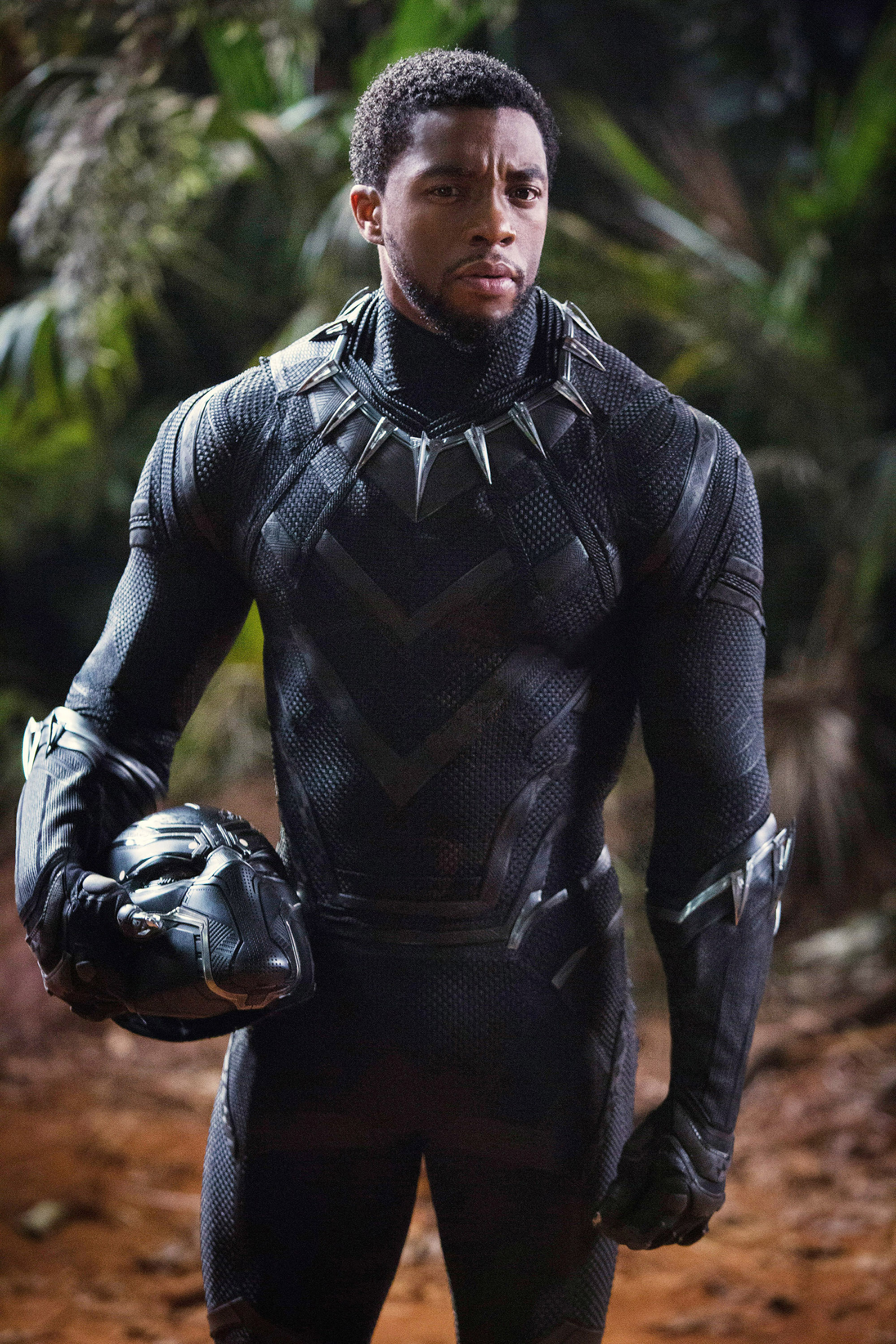 Chadwick Boseman as Black Panther holding his helmet