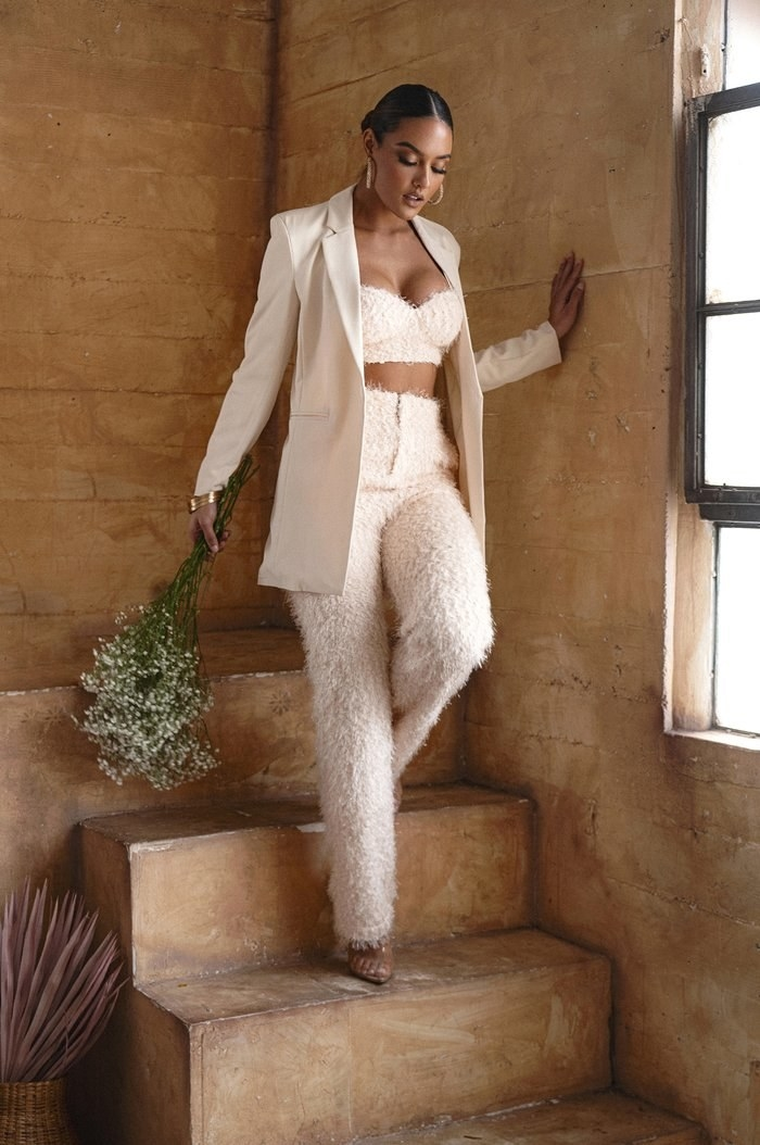 model wearing cream colored shaggy pants with a matching bralette under a blazer