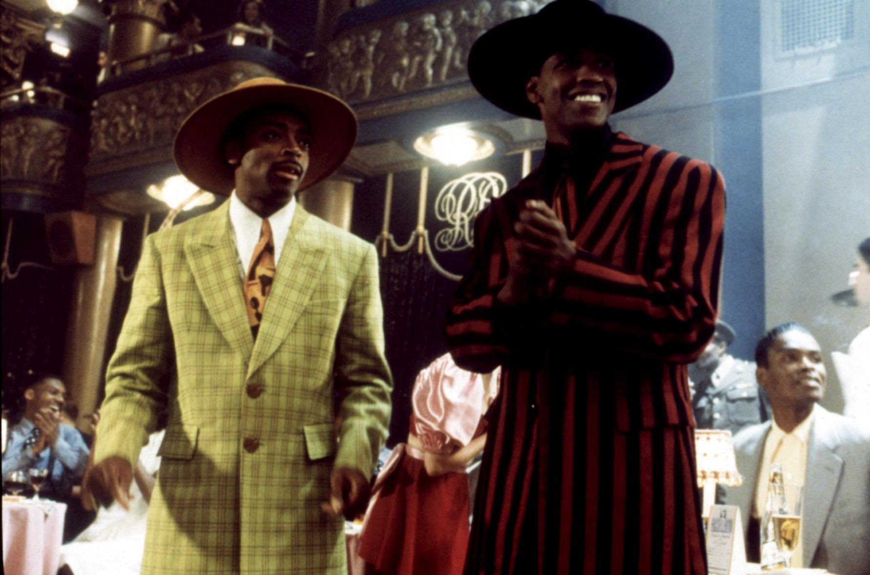 Spike Lee and Denzel Washington wearing zoot suits and matching hats in a scene from Malcolm X