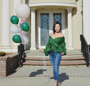 reviewer wearing the green version paired with jeans and heels