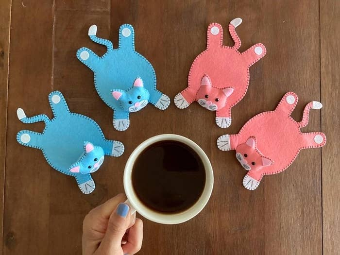 Model holding coffee cup with four cat-shaped coasters on table