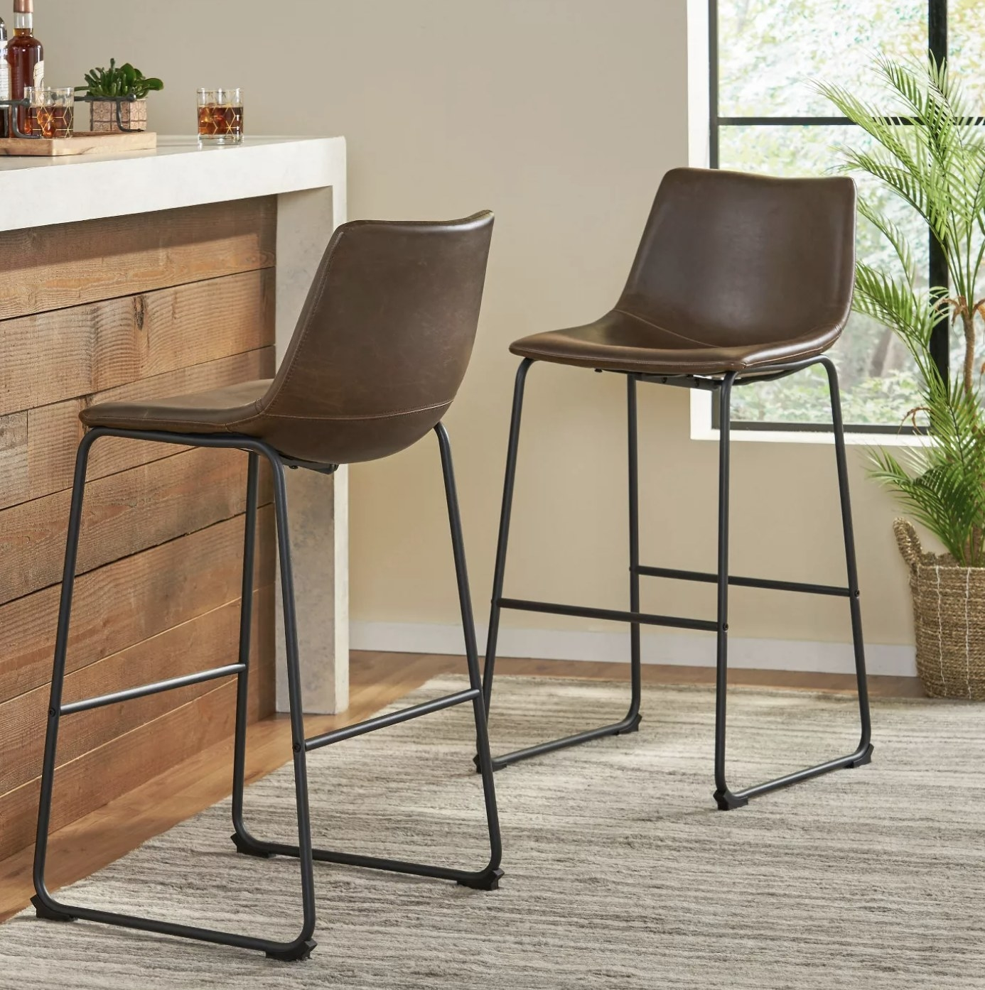 A set of two brown faux leather bar stools