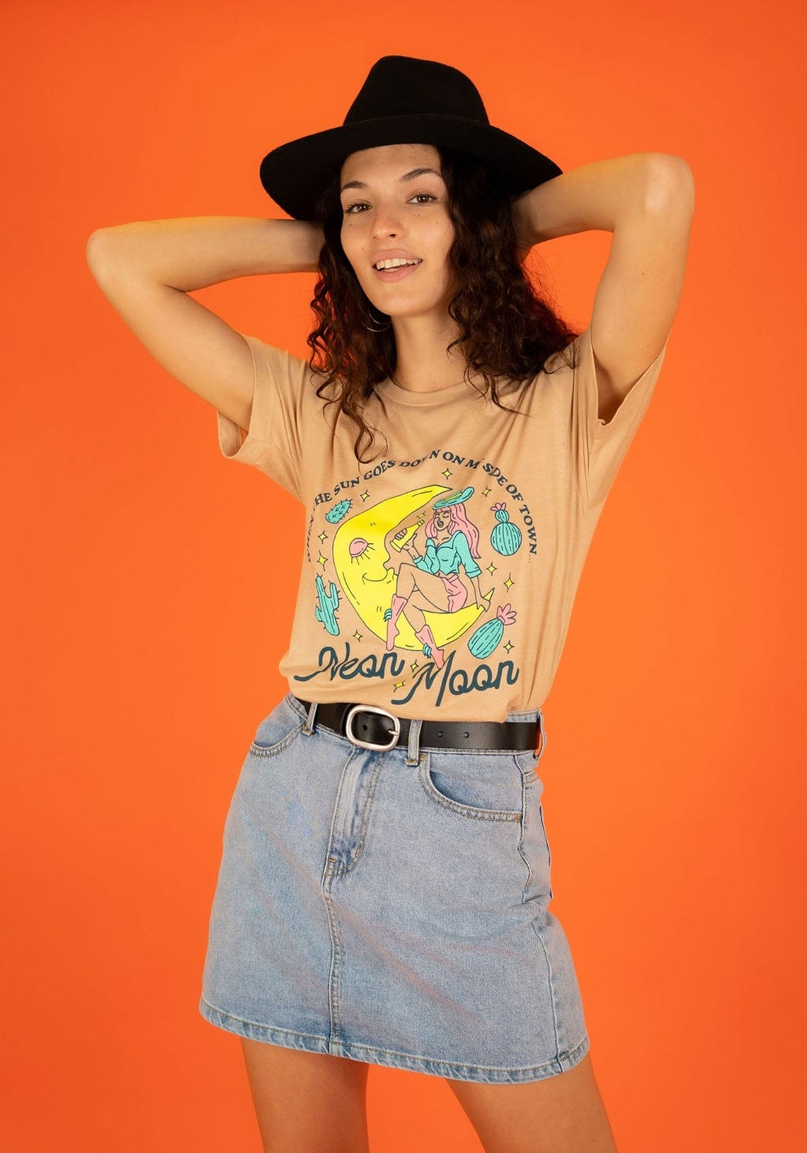 """model wearing illustrated tee with a cowgirl sitting on a moon drinking a lyrics from """"Neon Moon"""""""