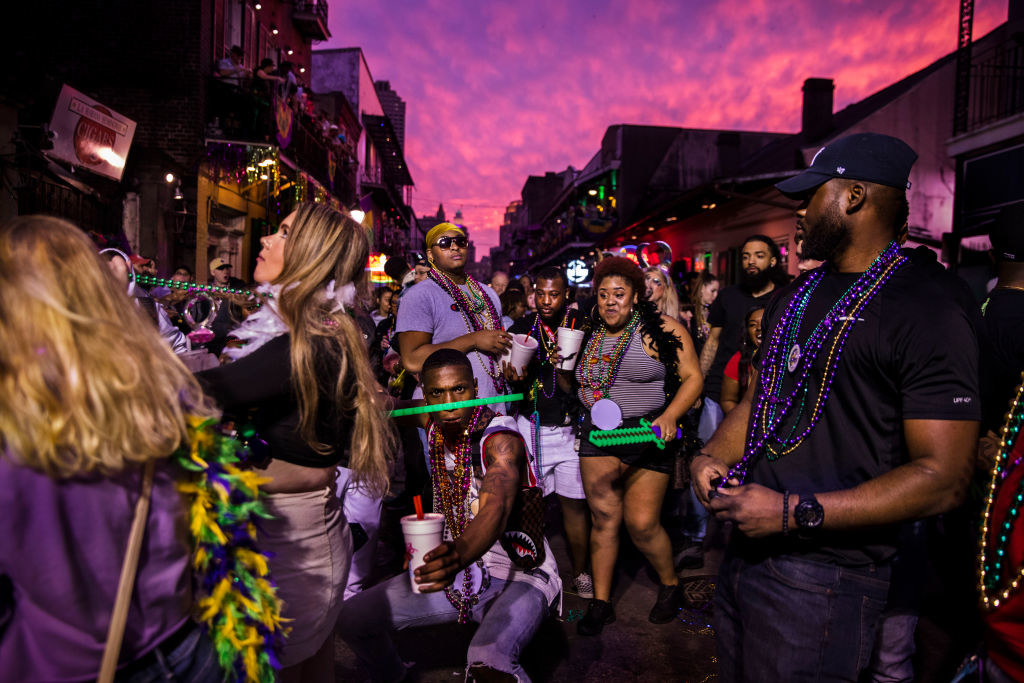 Bourbon Street filled with revelers wearing beads and feather boas as they drink and have a good time