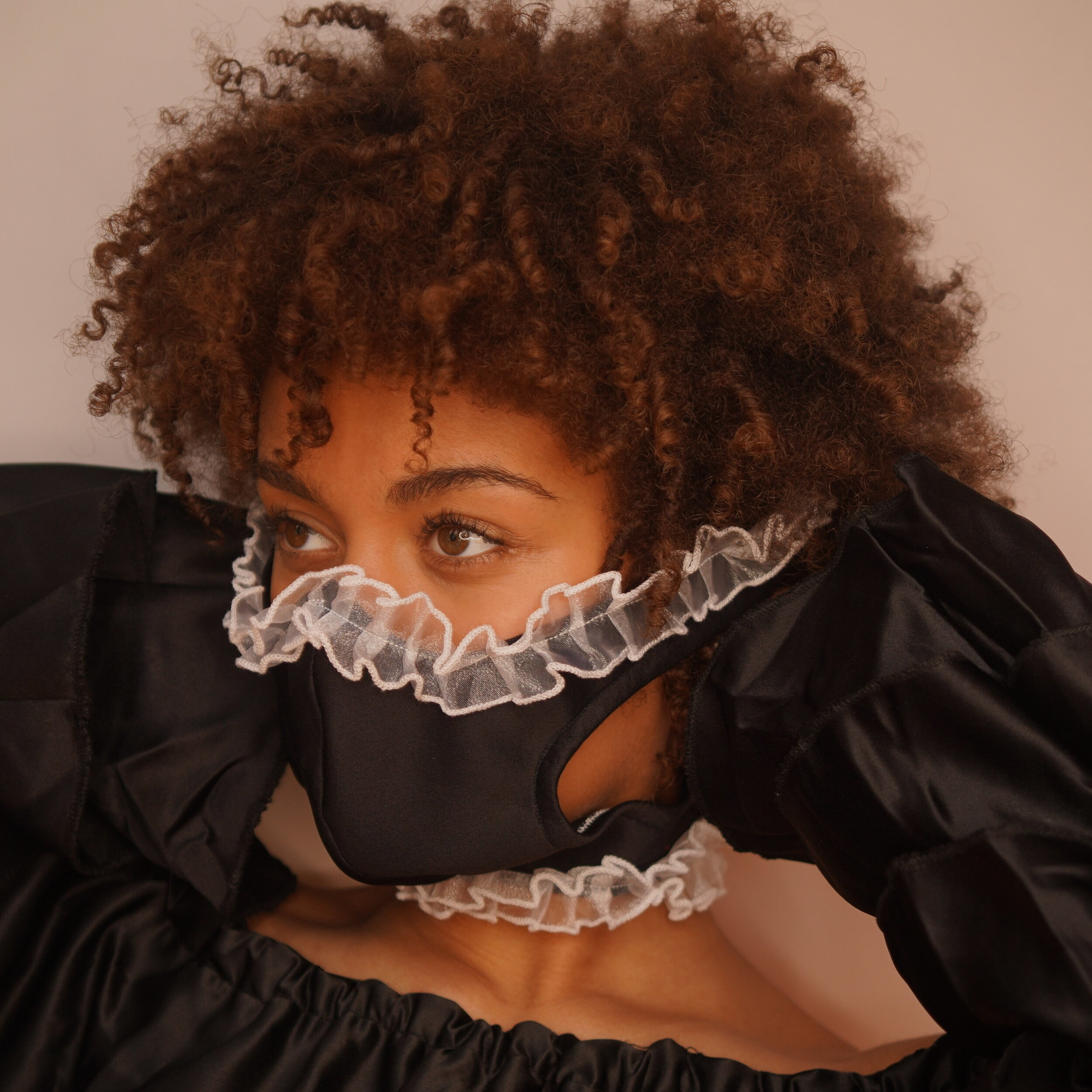 model wearing a black face mask with white ruffles as an accent