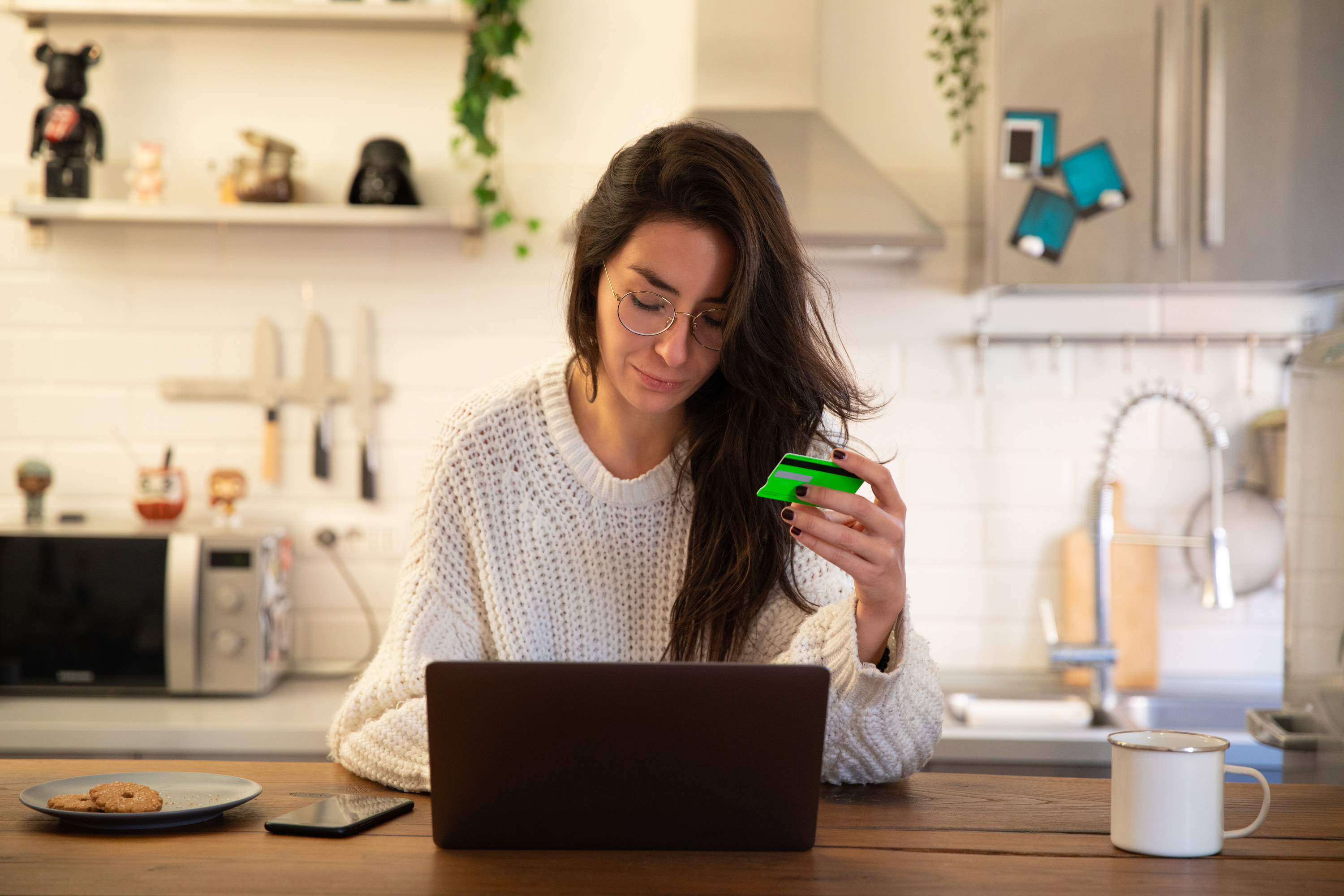 Women holding credit card while using laptop