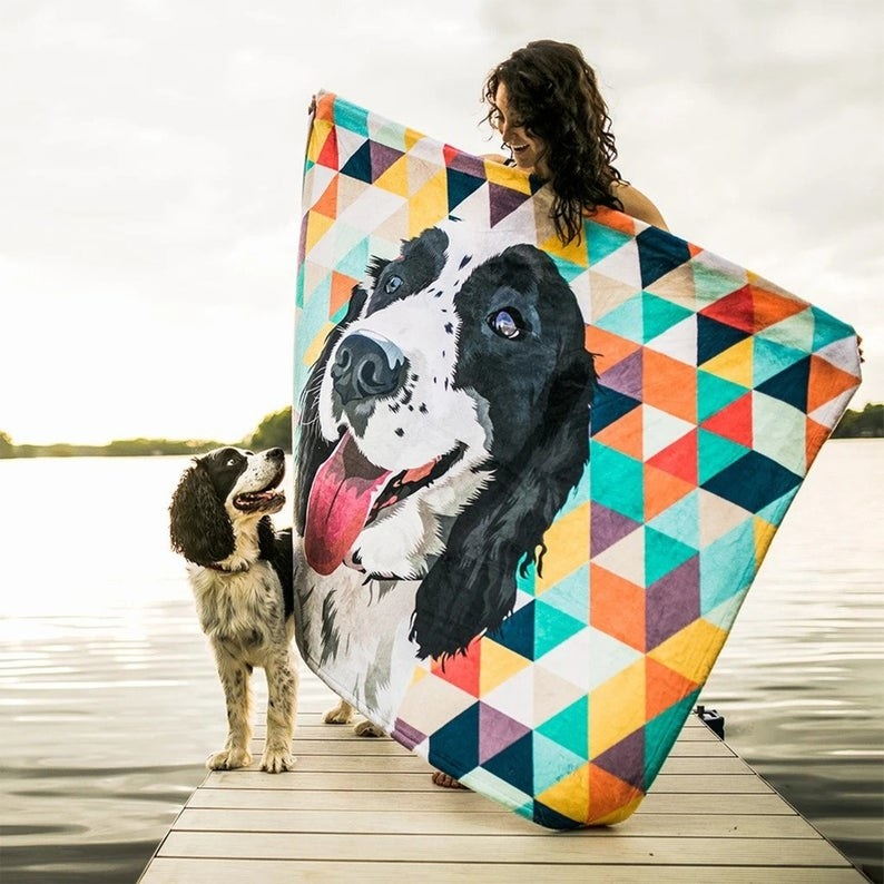 Spaniel standing next to a person holding a colorful geometric print with the dog's portrait on it