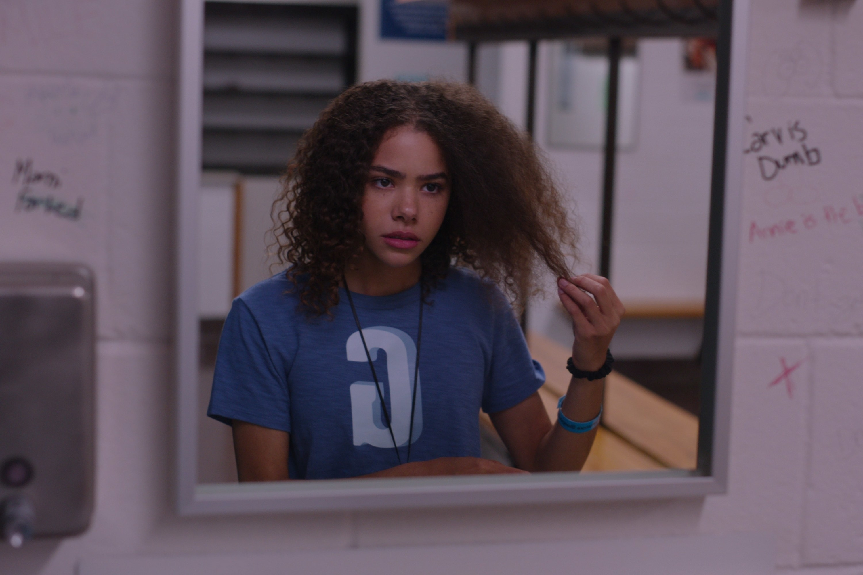 Ginny pulls at her curly hair in the mirror
