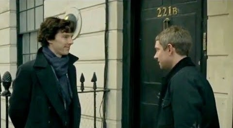 Sherlock and Watson standing in front of 221B Baker Street