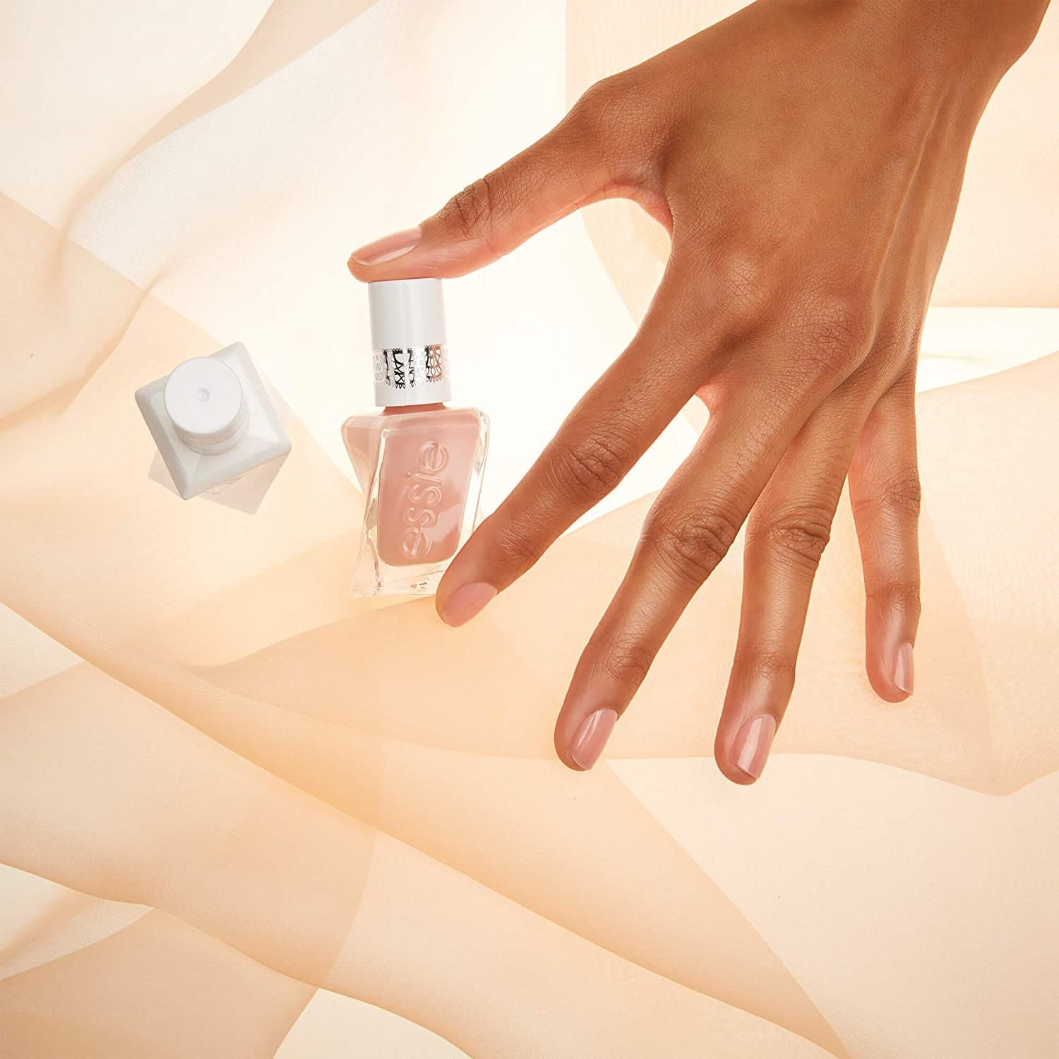 A person with painted nails holding a bottle of nail polish between their thumb and pointer finger
