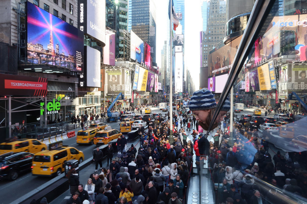 Times Square filled with people as taxis and other vehicles drive through