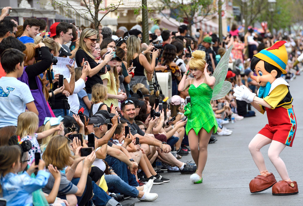 A large crowd lines a Disneyland street to watch the parade and interacts with Tinker Bell and Pinnochio