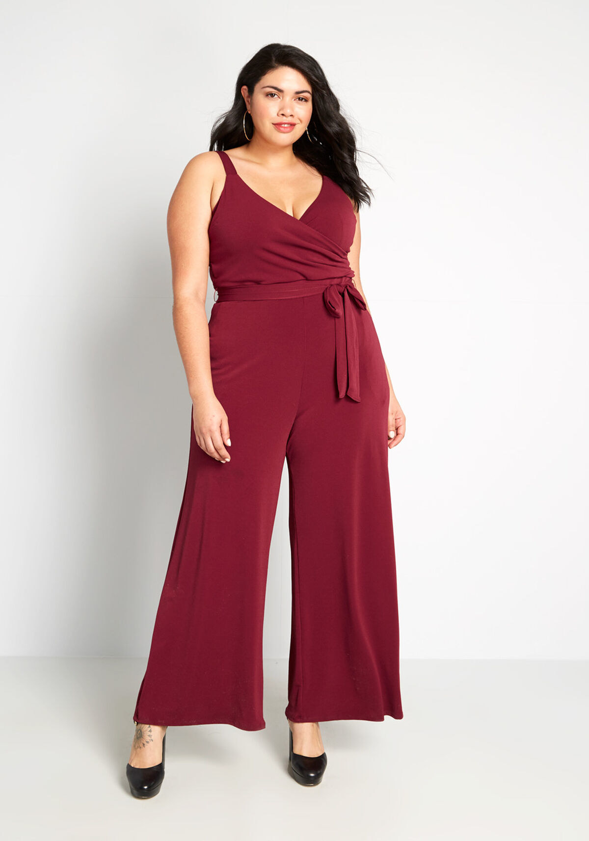 a model wearing the jumpsuit in burgundy