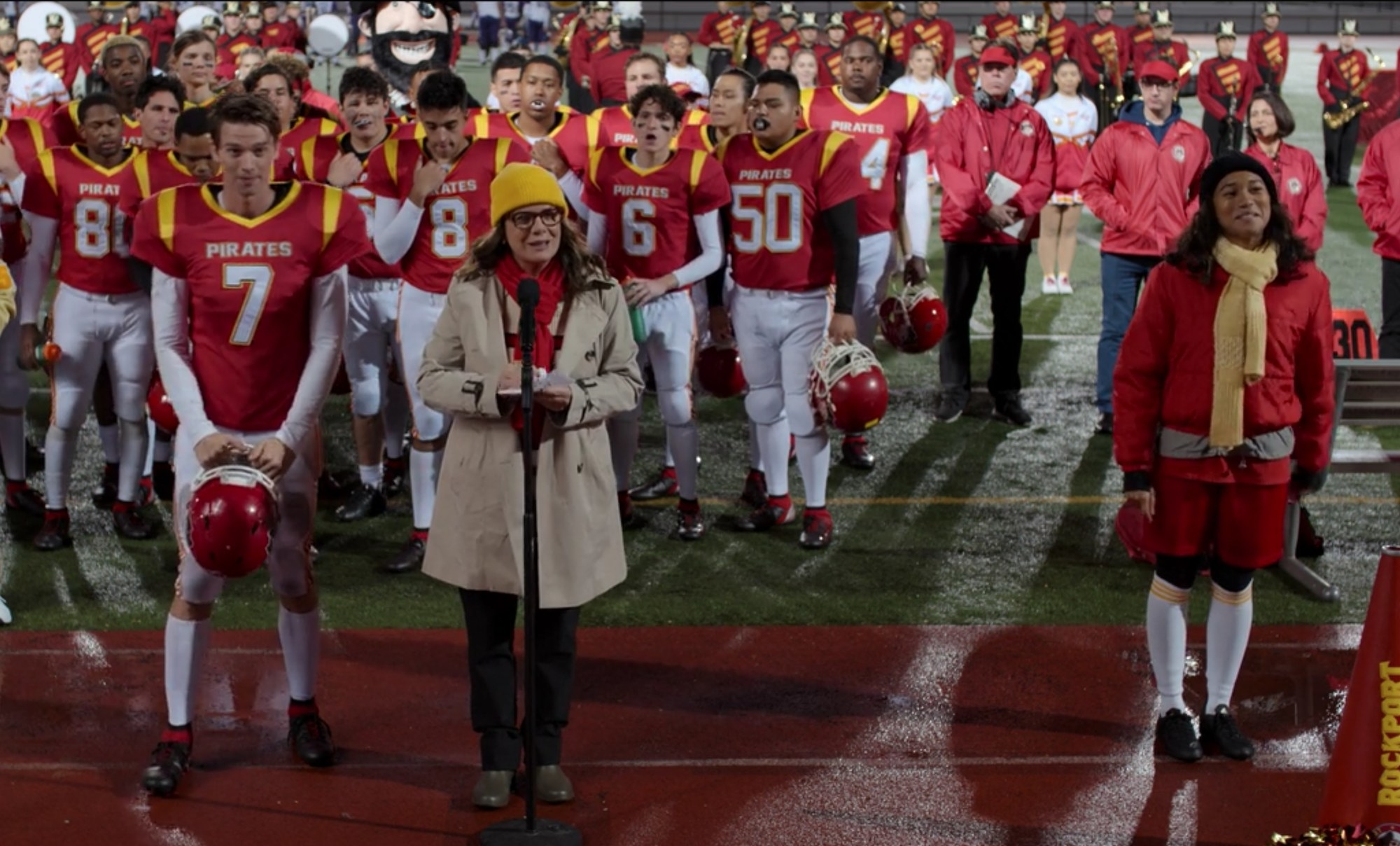 High school's football team stands on the field behind the principal at a microphone