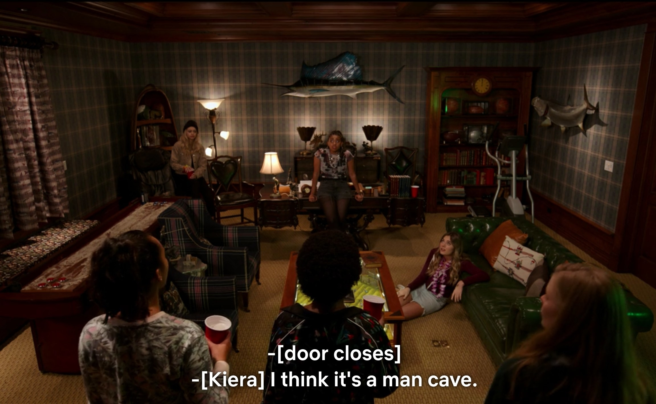 """Girls in the Moxie club gather in a dim room with plain, drab decorations, and Kiera says, """"I think it's a man cave"""" as the door closes"""