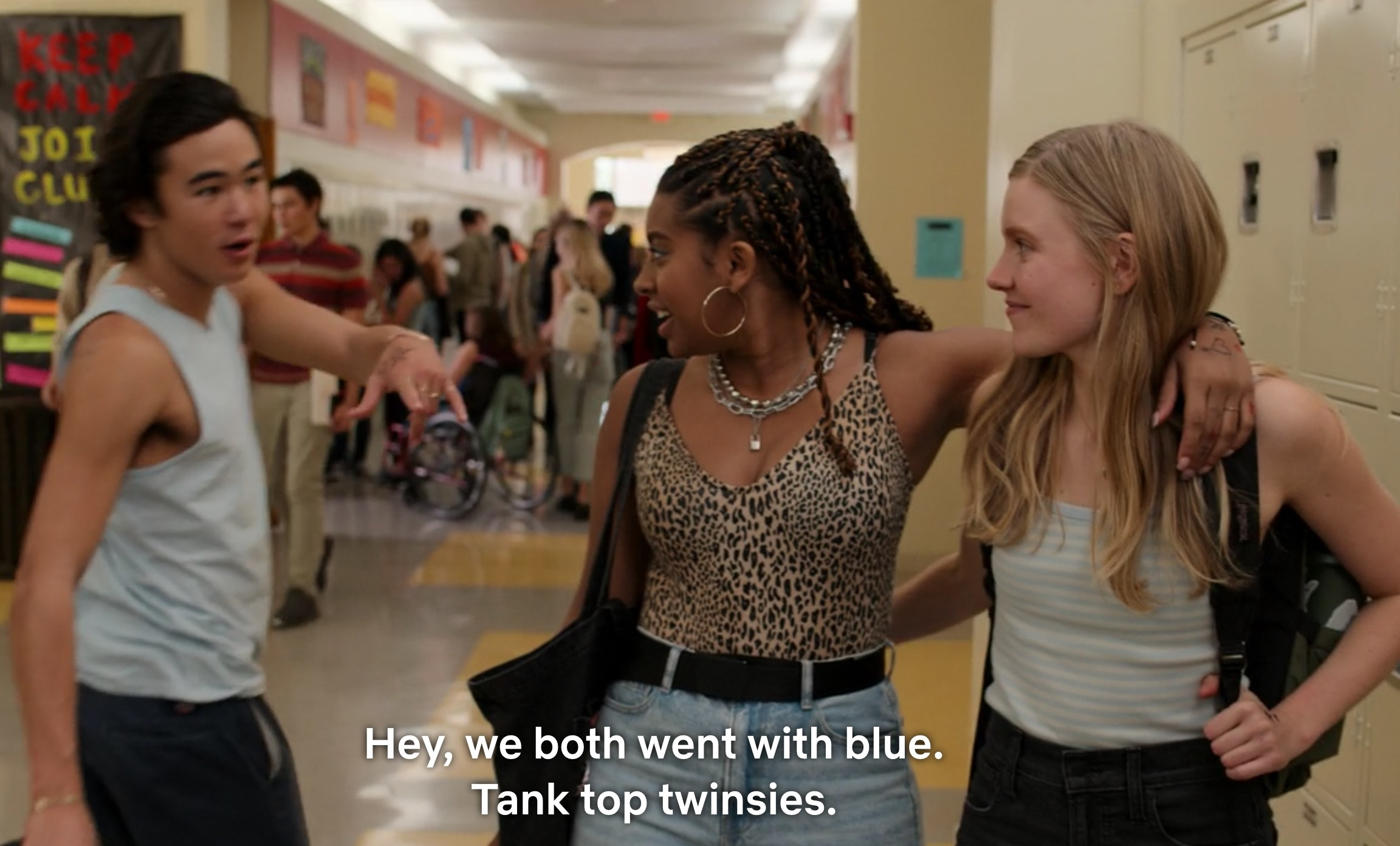 "High school girls with arms around each other say to Seth, ""Hey, we both went with blue; tank top twinsies"""