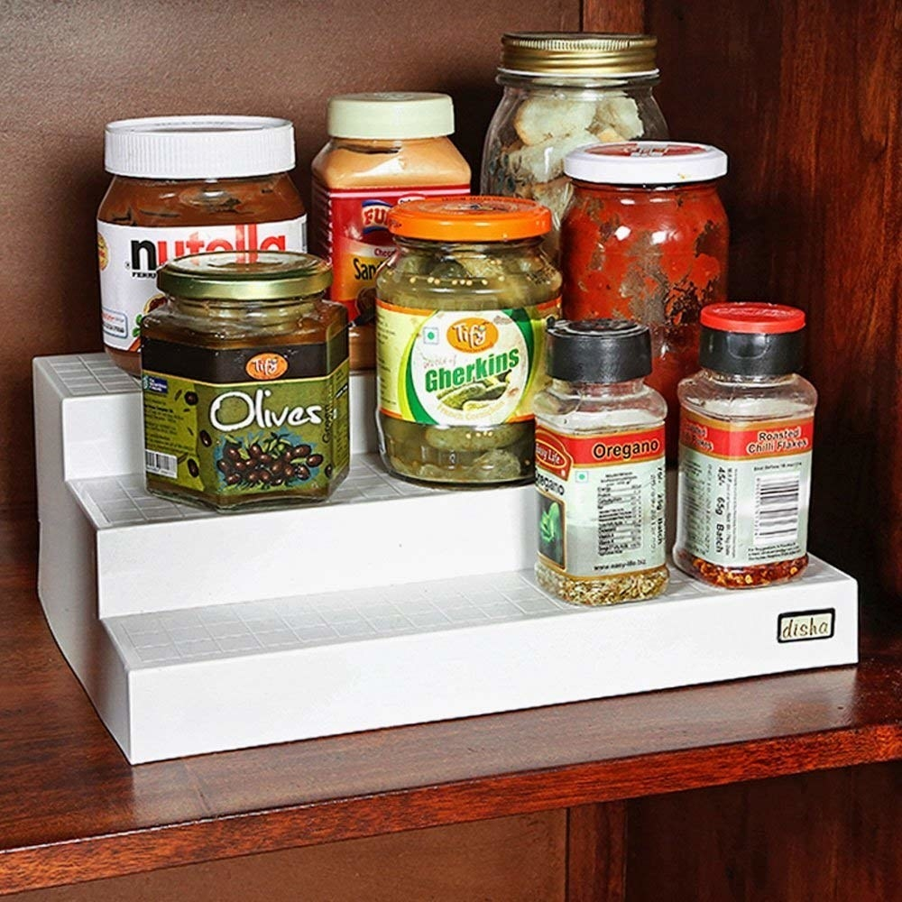 Three tier cupboard organiser with spices on it