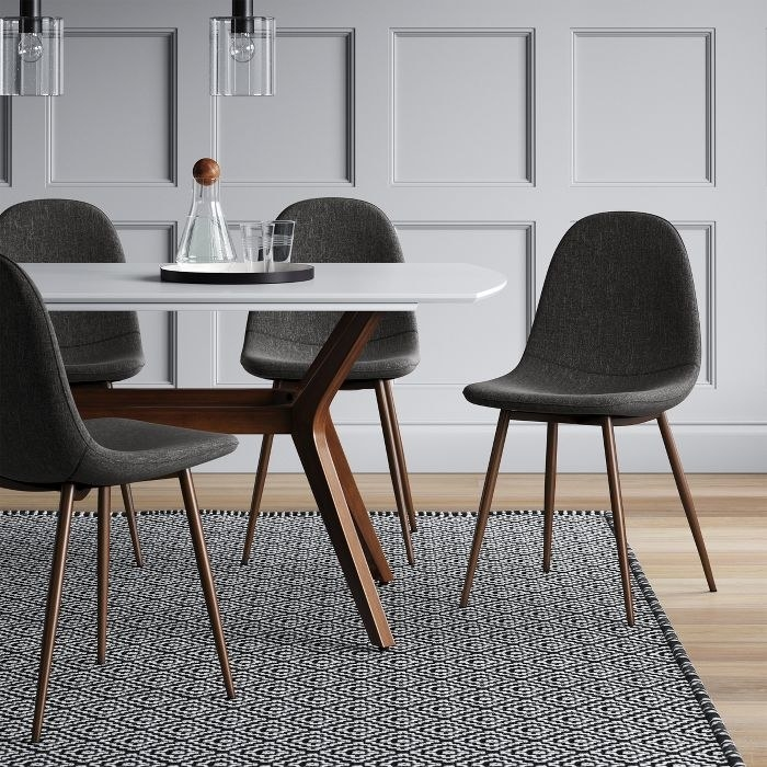 grey upholstered bucket seat dining chair with wooden legs next to a dining table