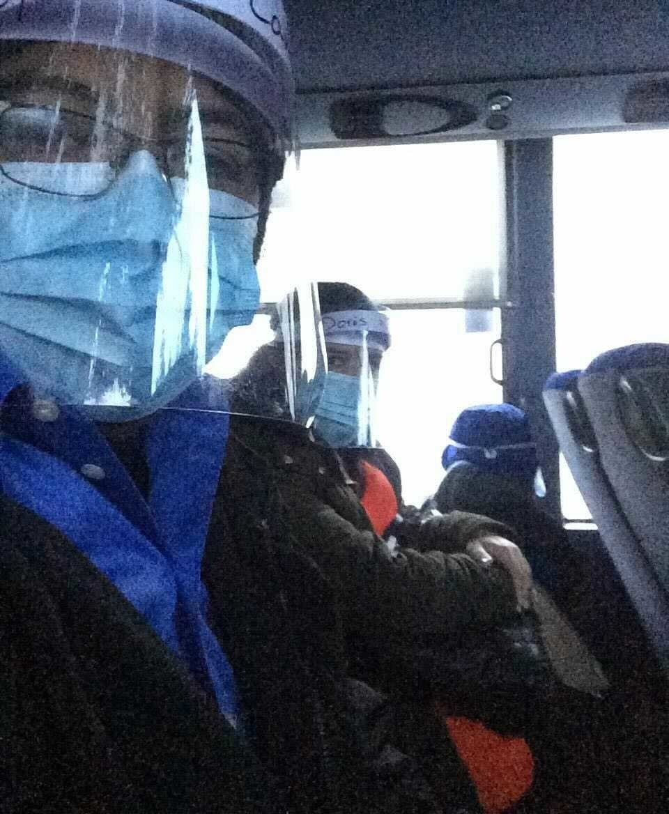 Two people on a bus with masks and face shields