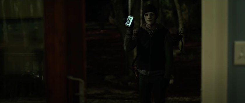 Man in a mask holding up a phone.