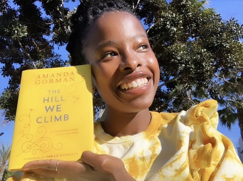 """Amanda smiling and holding her book """"The Hill We Climb"""""""