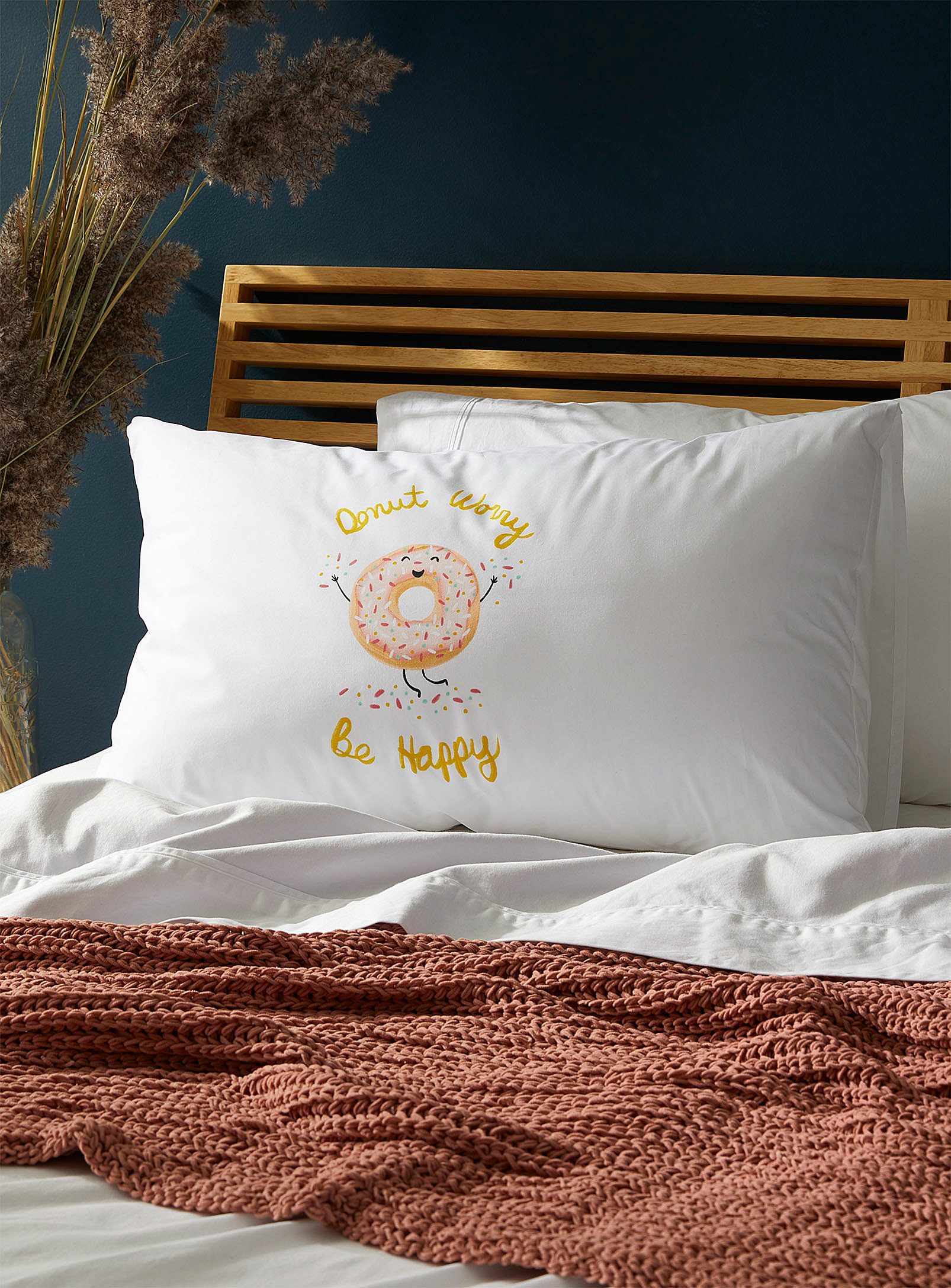 A pillow on a bed that has an illustration of a donut and a message that says donut worry be happy