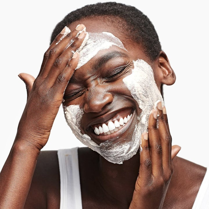 A woman smiling with a skincare product on her face