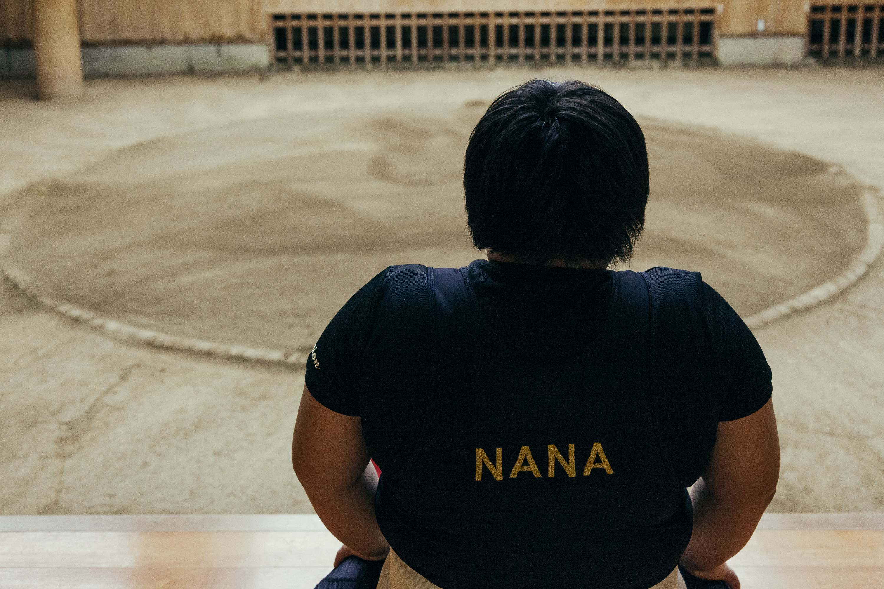 A young girl at the edge of a sumo practice ring wearing a shirt with her name on it, Nana