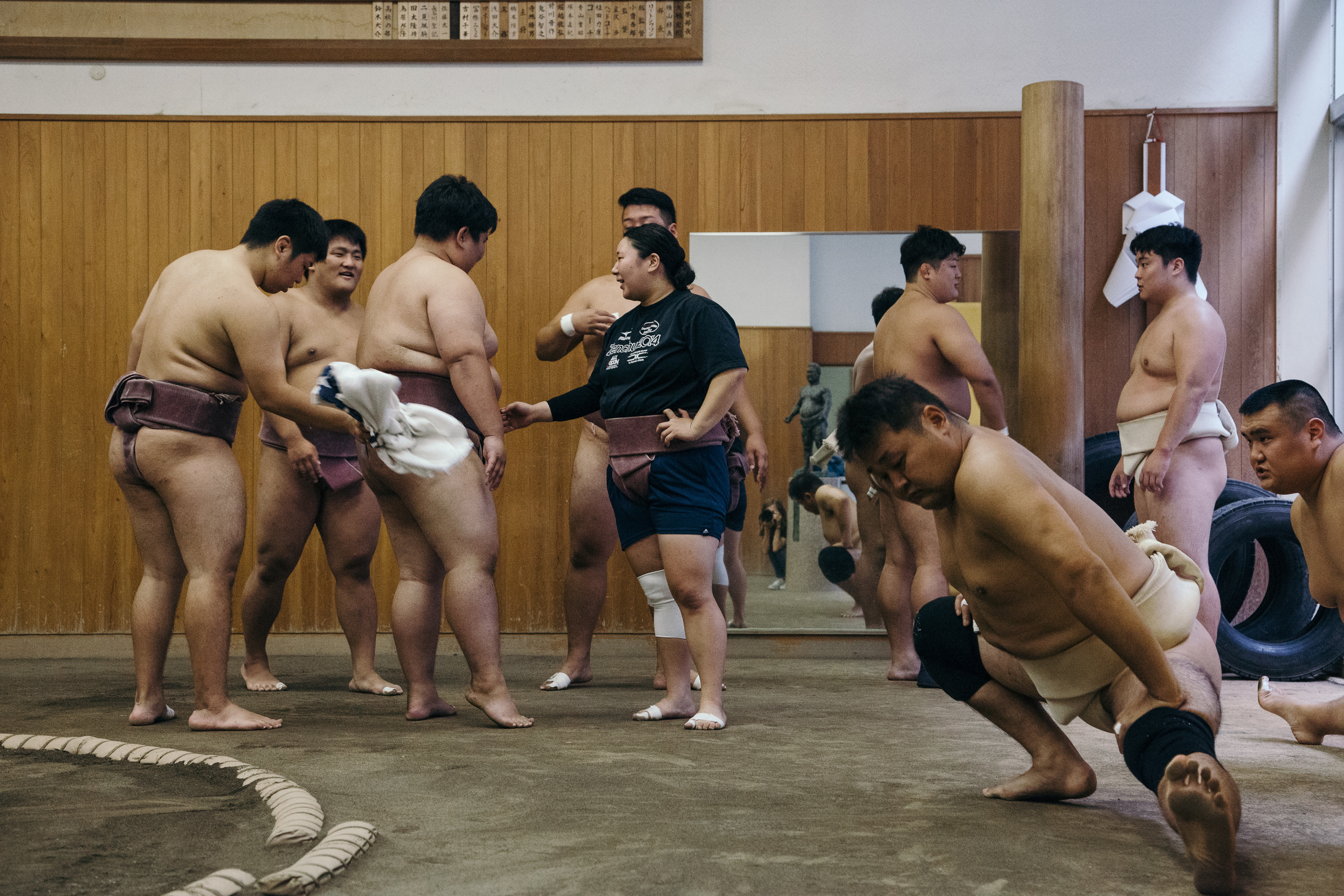 A female sumo wrestler in a practice room with a bunch of male sumo wrestlers