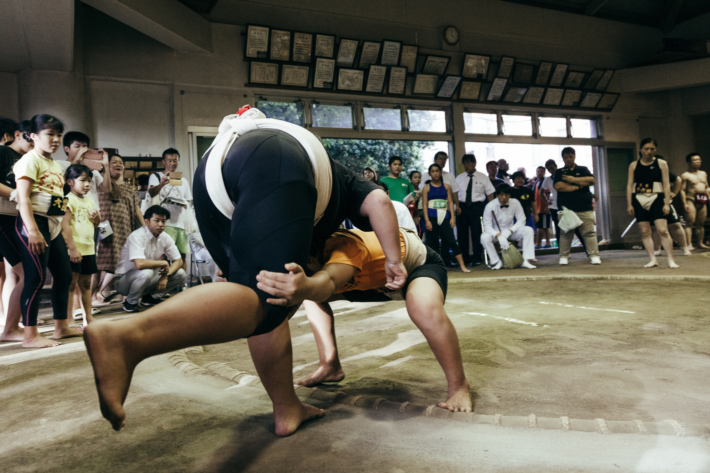 Two young girls fighting in a sumo ring with a crowd around them