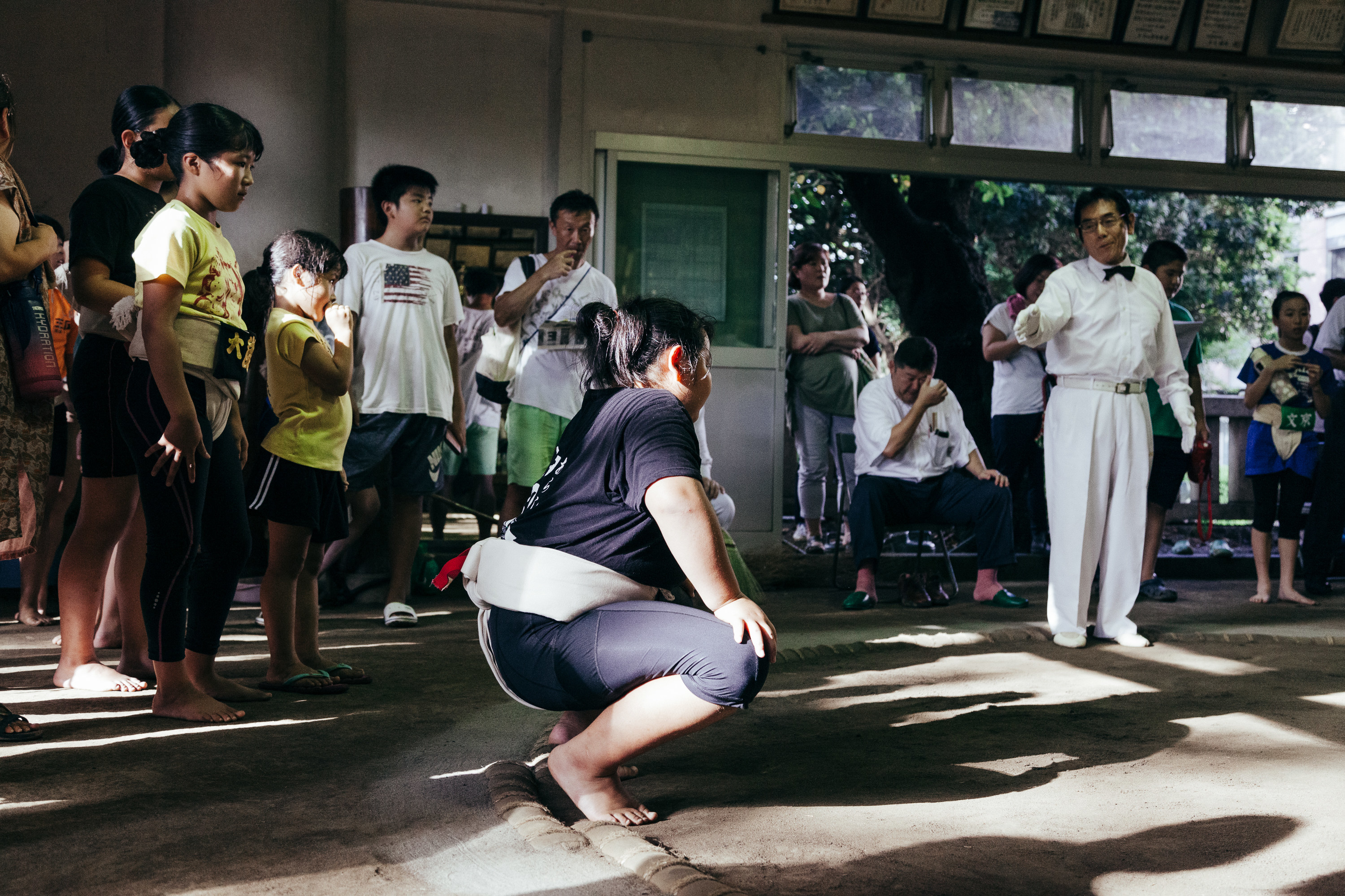 A girl crouches at the end of a sumo ring in front of a crowd