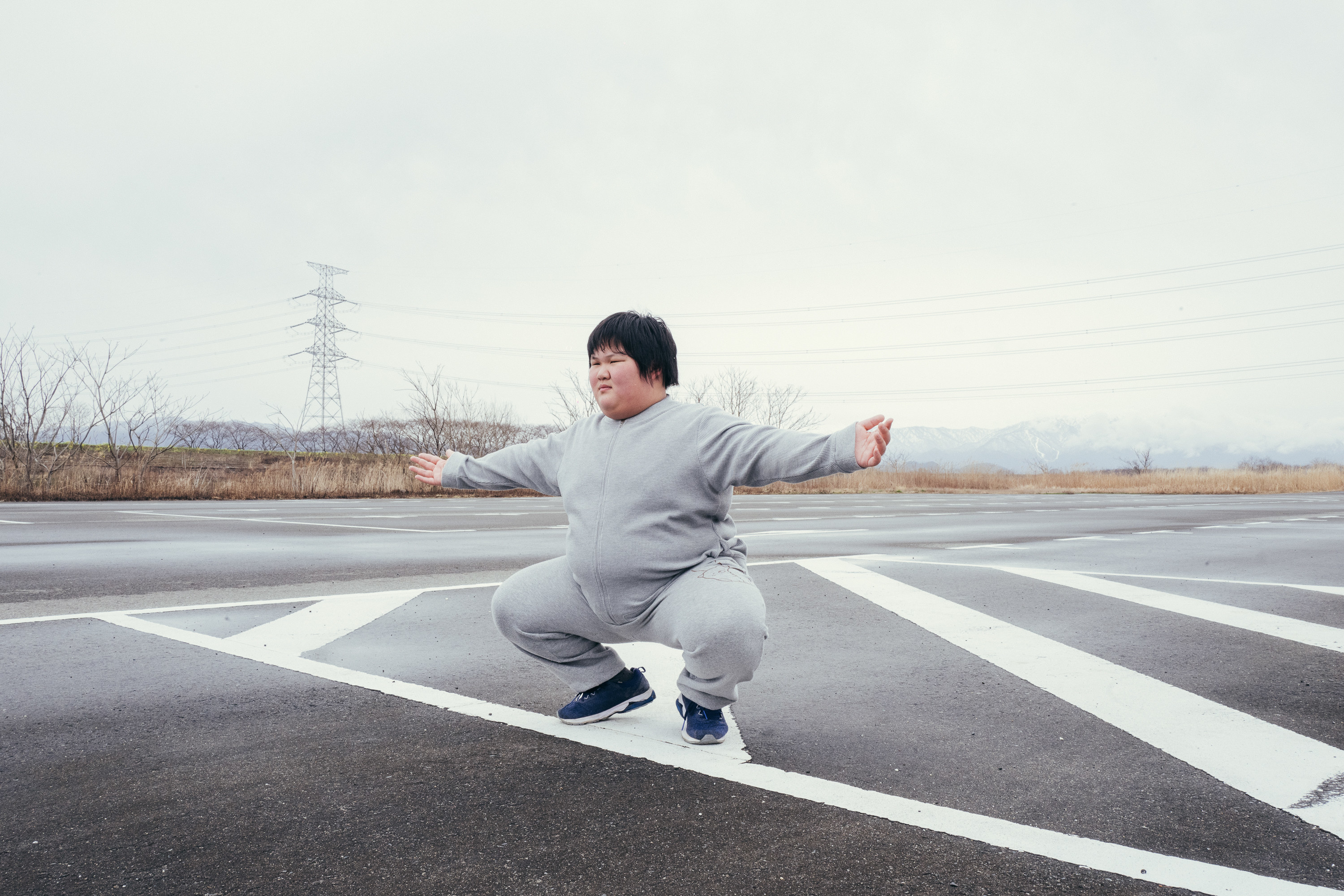 A young sumo wrestler crouches in a parking lot