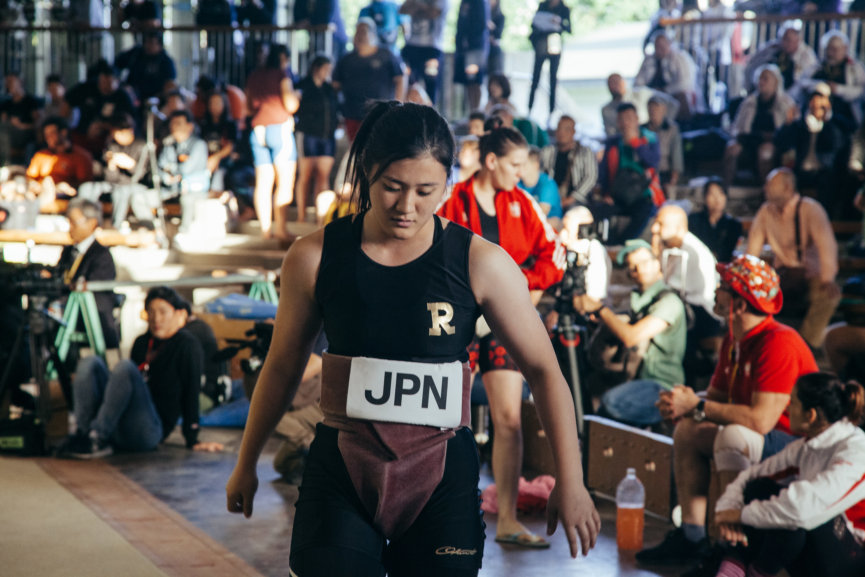 a female sumo wrestler in front of the crowd with a Japan country label