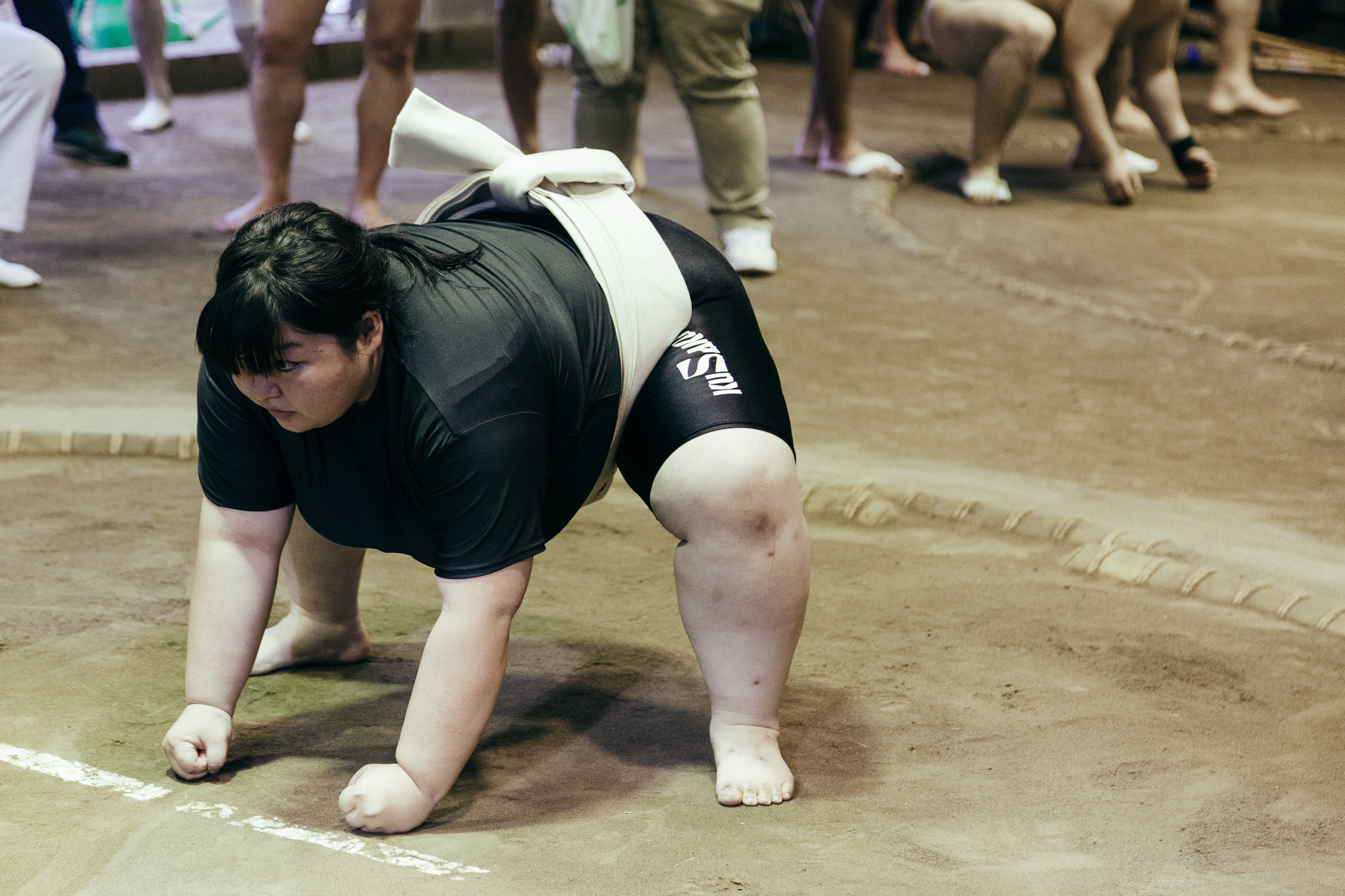A young female sumo wrestler crouches at the edge of a ring
