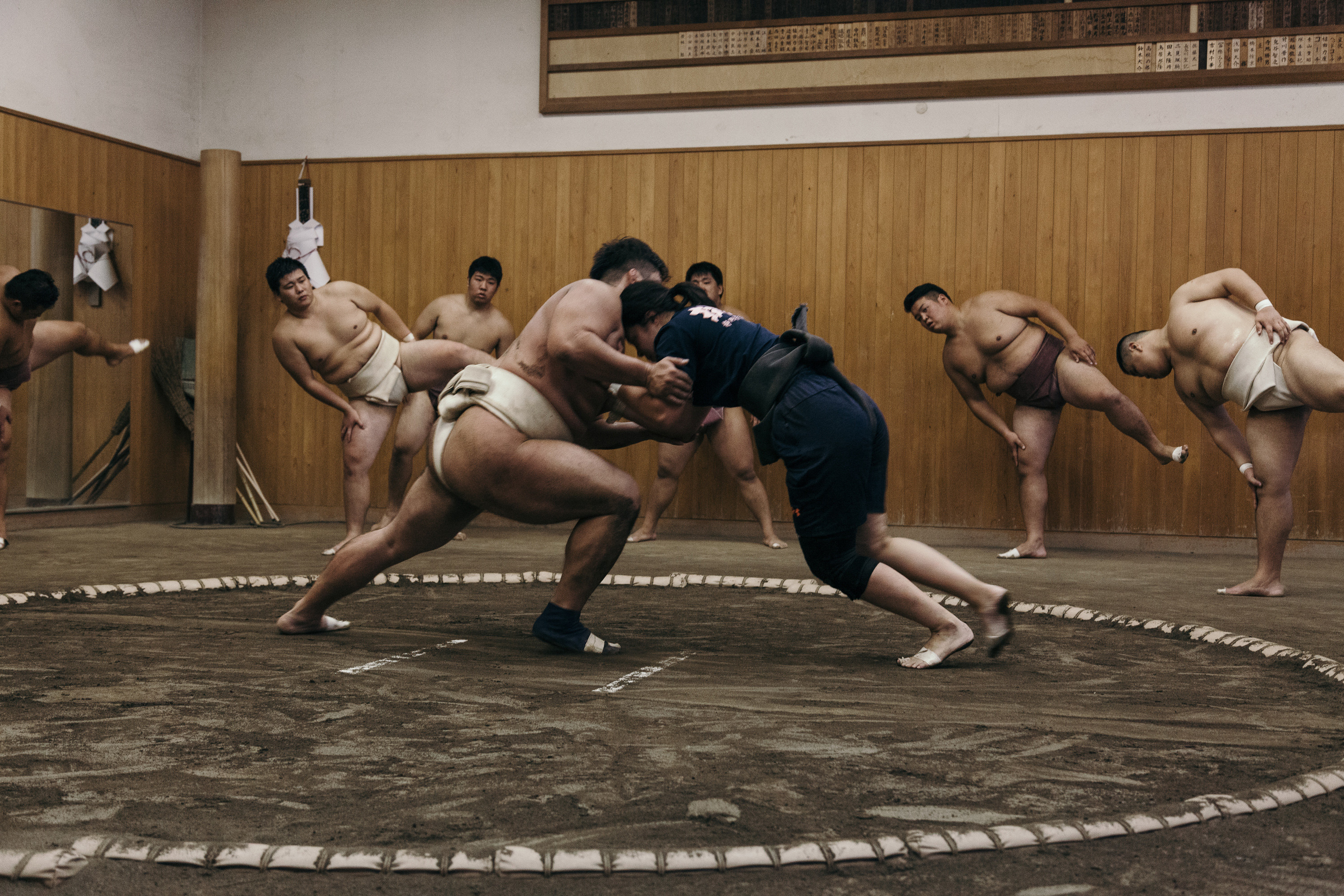 A young female sumo wrestler faces off with a male wrestler as other people exercise in the background