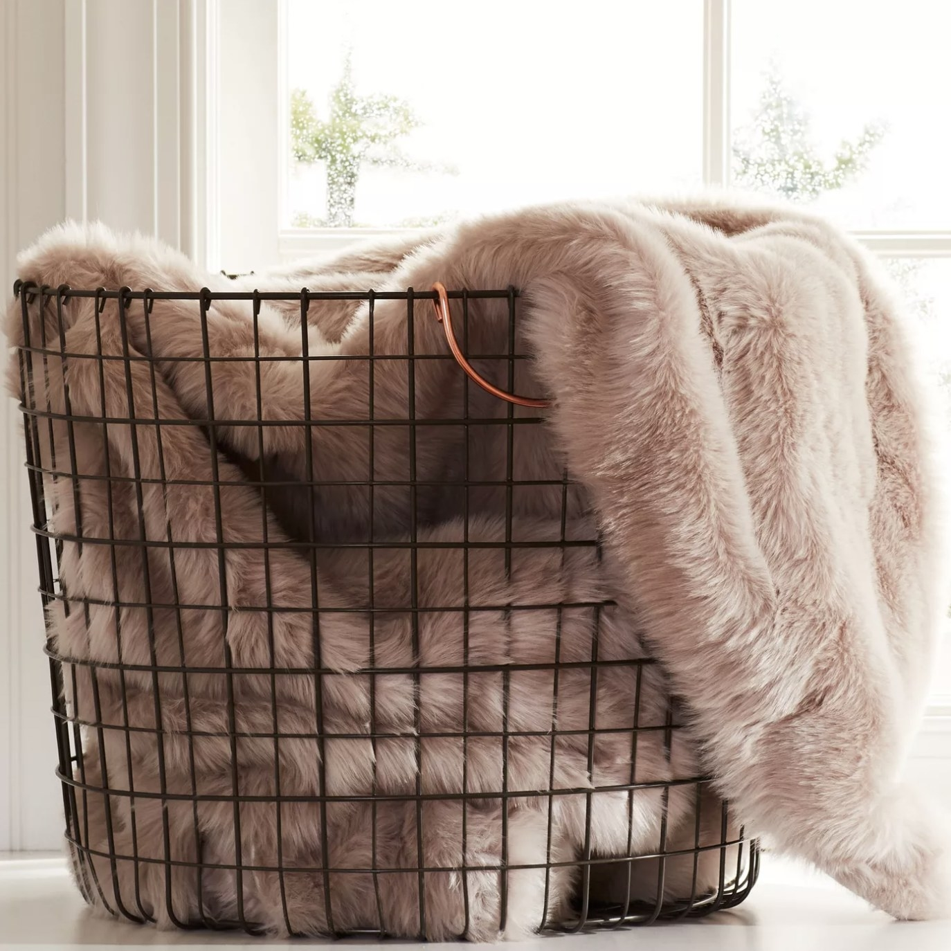Wire basket with blanket in it.