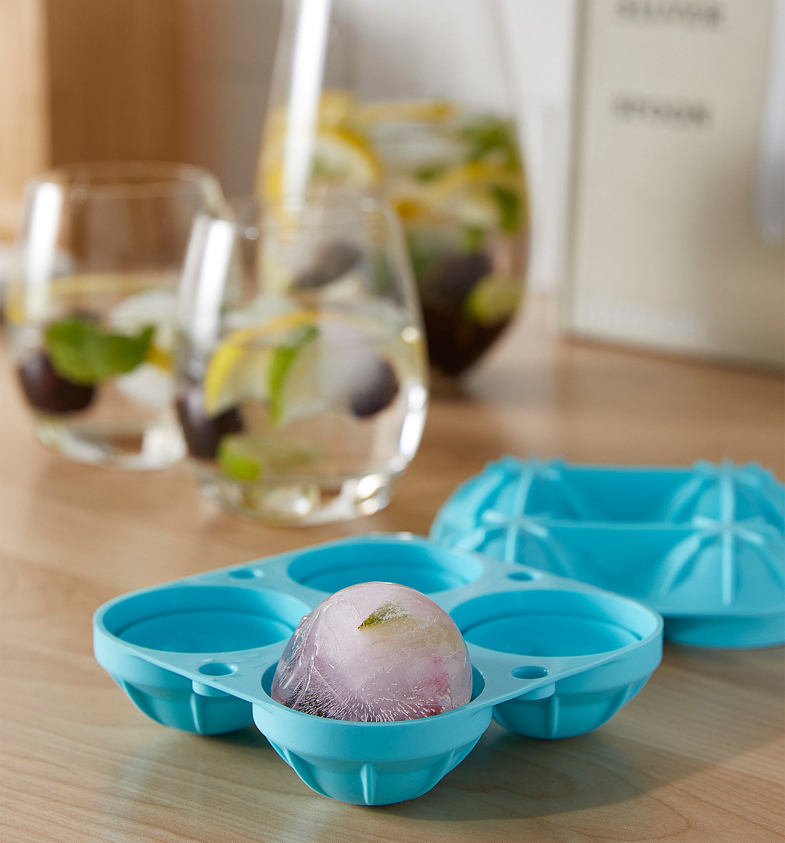 A silicone ice cube tray with a round block of ice in one slot